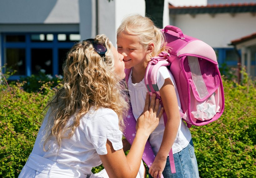 Mother kissing daughter before school